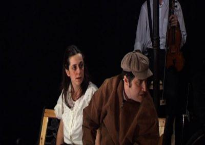 extrait de la pièce de théatre SS avec S ou l'on voit deux comédiens interprétant leurs personnages respectifs, ainsi qu'un musicien en arrière plan. Image faisant partie d'un diaporama de photos de différentes scènes de la pièce de théatre SS avec S..