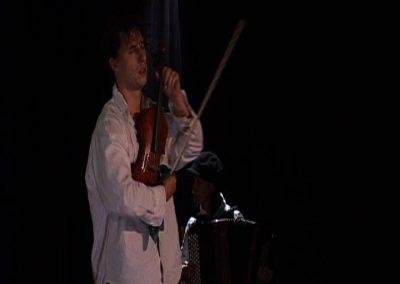 Photo d'un violoniste en premier plan et d'une accordéoniste en second plan dans une scène de la pièce de théâtre SS avec S. Image d'un diaporama de divers photos, extrait de la pièce.