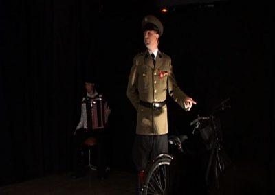 Scène de la pièce de théâtre SS avec S ou l'on voit un comédien interprétant un nazi et une musicienne jouant de l'accordéon en second plan.